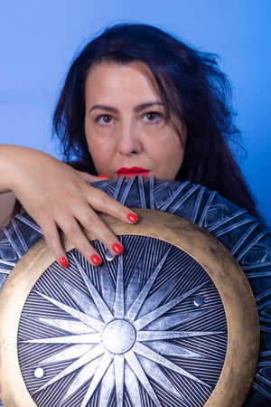 Portrait of a European woman with a shield and sword in her hands. Shooting in the studio. Close-up, red lipstick, model in black dress.