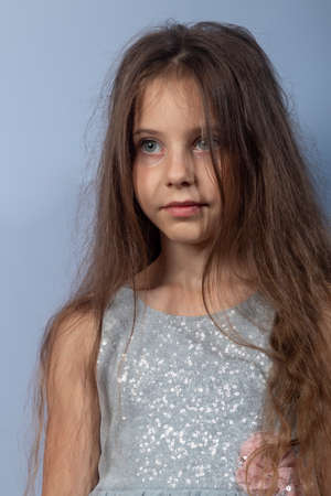 Portrait of a little beautiful girl with long hair. In a gray dress with sequins on a light background. Front view.