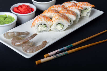 Sushi Sets Uramaki,  Philadelphia, on a white plate. Nearby ginger and wasabi. Soy sauce in a white bowl. On a dark background. Copy space. 스톡 콘텐츠