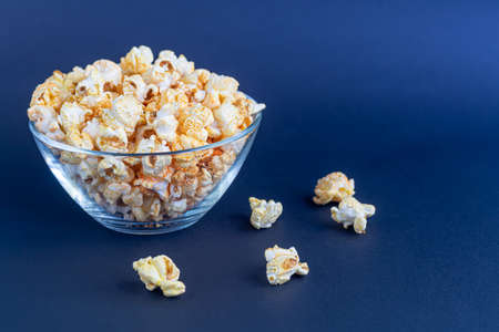 A clear bowl of popcorn on the darkened surface. Copy space.