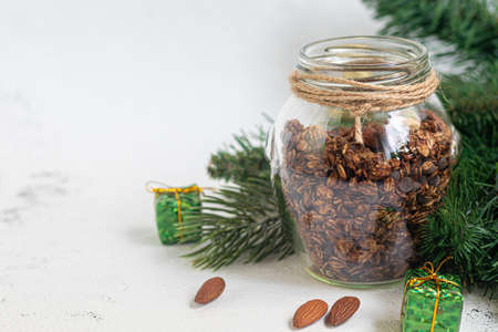 Homemade granola with chocolate and nuts in a glass jar. New year concept. On a gray background. Vegetarian dish. Copy space.