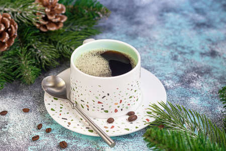 A cup of delicious aromatic coffee. It is placed on a substrate made of coffee beans. New Year holiday concept. On a light background. Copy space.