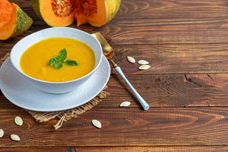 Fresh pumpkin cream soup with sour cream. Autumn lunch concept. On a wooden background. A dietary, healthy dish. Copy space.
