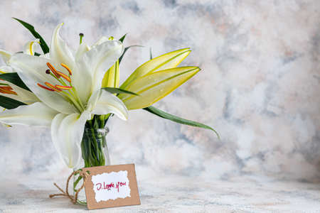 A bouquet of lilies on a light background. Mother's Day, Women's Day, Valentine's Day or Birthday. Copy space. Stok Fotoğraf - 163747036