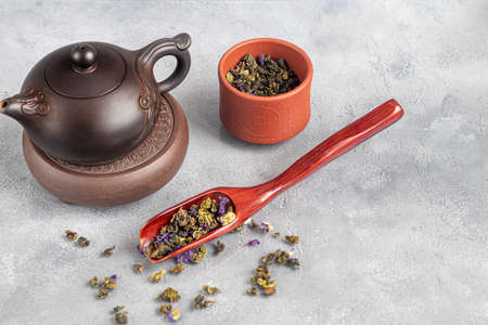 Tea in a cup and in a teapot. Chinese tea, health and benefits. Chinese pu-erh in a bowl. In the background is a brown teapot and tea leaves. Copy space. Stok Fotoğraf - 164056421