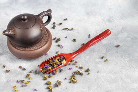 Tea in a cup and in a teapot. Chinese tea, health and benefits. Chinese pu-erh in a bowl. In the background is a brown teapot and tea leaves. Copy space. Stok Fotoğraf - 164056422