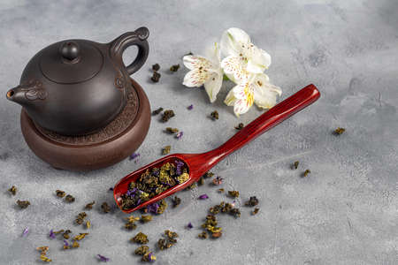 Tea in a cup and in a teapot. Chinese tea, health and benefits. Chinese pu-erh in a bowl. In the background is a brown teapot and tea leaves. Copy space. Stok Fotoğraf - 164056424