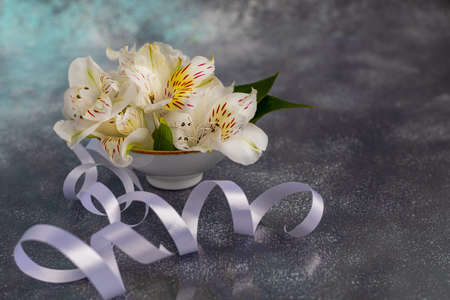 A bouquet of wild orchids on a light background decorated with ribbons. Mother's Day, Women's Day, Valentine's Day or Birthday. Baner. Copy space. Stok Fotoğraf - 164056453