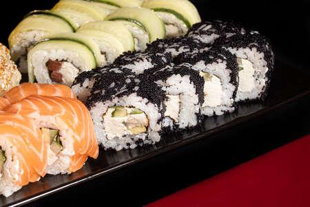 Sushi Sets Uramaki, California, Philadelphia, on a white plate. Festive new year concept. Against a dark reflective background. Copy space. Stok Fotoğraf - 164822881