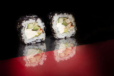 Sushi Sets Uramaki, California, Philadelphia, on a white plate. Festive new year concept. Against a dark reflective background. Copy space. Stok Fotoğraf - 164822652