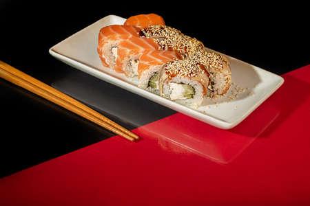 Sushi Sets Uramaki, California, Philadelphia, on a white plate. Festive new year concept. Against a dark reflective background. Copy space. Stok Fotoğraf - 164823027