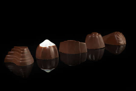 Chocolate candies on a dark background with reflection. Piece by piece and as a whole. Filling of nuts and fruits. Copy space.