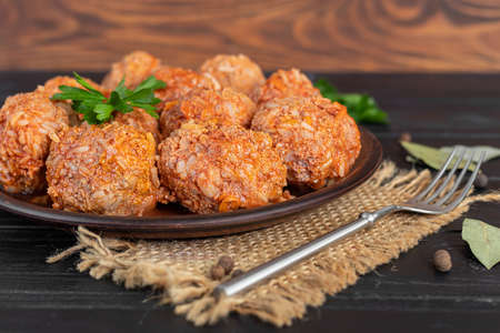 Meat balls on a wooden background with sage and parsley leaves. Homemade lunch. Copy space.