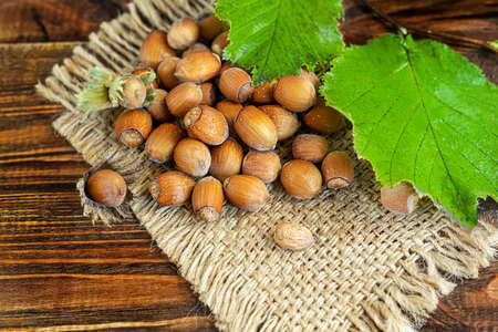 Hazelnuts on a wooden background with green leaves. Contains beneficial vitamins and minerals. Copy space.