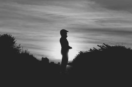 Woman silhouette in a sporty autumn outfit highlighted by the setting sun with gorgeous clouds in the sky in black and white colors Stock Photo