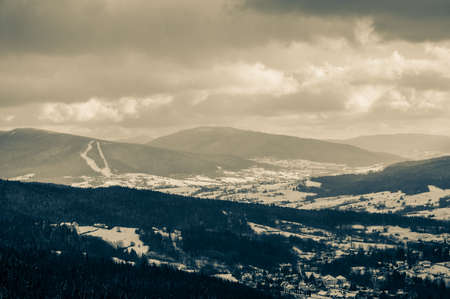 Great view of the village in the snow between forest and the mountains on a cloudy day.