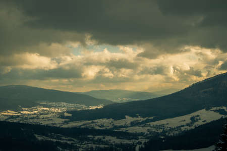 The sun breaking through the thick gray clouds illuminating the snowy village and mountains