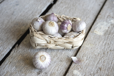 wooden basket: Garlic in basket on wooden table Stock Photo