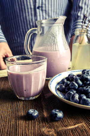 Yogurt in a glass, blueberries, lavender, pitcher. male hands Stock Photo