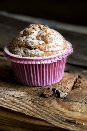 Cupcakes on an old textured Board. Dusted with powdered sugar Stock Photo