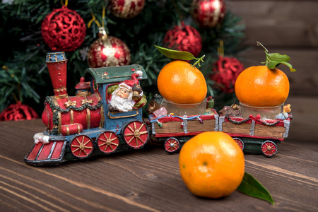 Christmas train carries tangerines. On the background of Christmas tree with balls