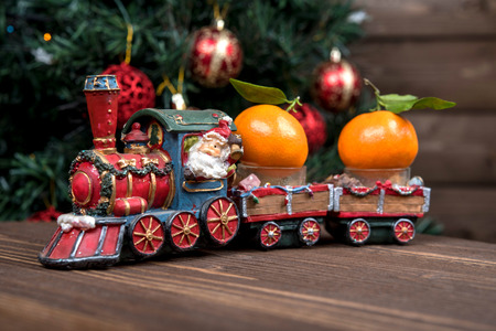 christmas train: Christmas train carries tangerines. On the background of Christmas tree with balls