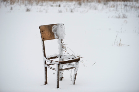 Abandoned, broken, broken-down old wooden chair in the winter in nature Stock Photo
