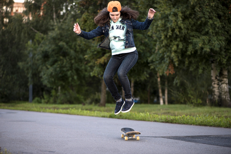 skate park: Young girl riding on a skateboard and jumping
