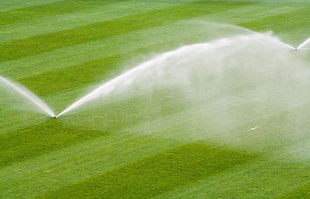 Water jets sprinkling a soccer stadium field.