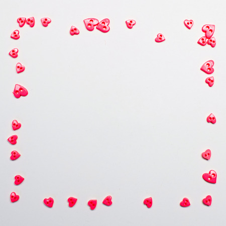 Small pink hearts on the perimeter on a white background with empty space and space to insert text