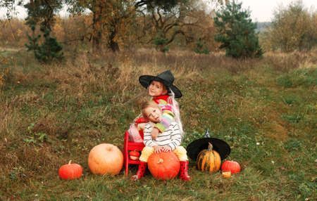 two girls are sitting on a meadow and hugging each other around them a lot of big and small pumpkins Halloween theme. A girl in a big wizard's hat is sitting on a pumpkin.