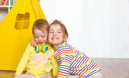 children play on the floor in the children's room. Two girls collect wooden cubes.