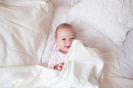 the child is lying in a cozy bed and laughing. The kid saw his mother.