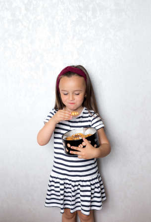 a little girl in a striped t shirt with black and white stripes is standing against the wall eating cookies from a large box