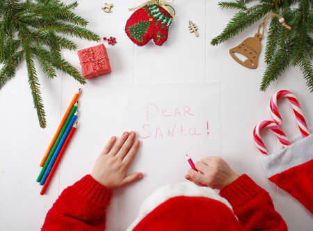 A little girl in a red Christmas hat writes a letter to Santa Claus