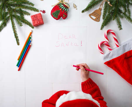 A little girl in a red Christmas hat writes a letter to Santa Claus Stock Photo