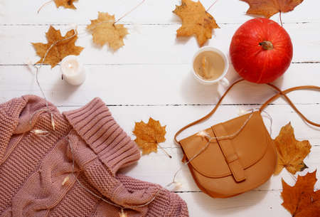 autumn still life, yellow leaves, pumpkin, candles, knitted sweater on a white background, top view.