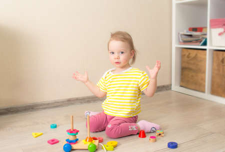 beautiful little child plays with wooden cubes. Kid playing on the floor in the children's room.