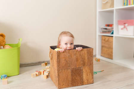 beautiful little child plays with wooden cubes. Kid playing on the floor in the childrens room