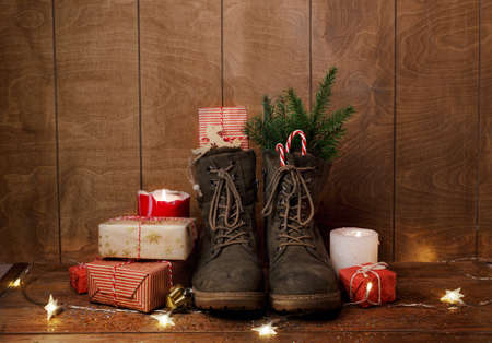 Christmas shoes on a wooden background around gifts, burning candles, green fir branches. Christmas still life.