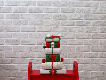 Christmas gifts in bright ribbons are stacked against a brick wall. Red and green ribbons with ornaments. Zdjęcie Seryjne