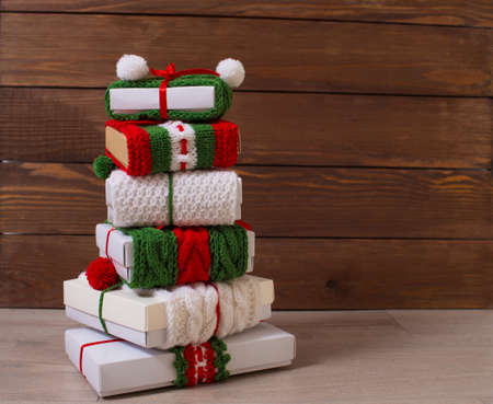 Christmas gifts in bright ribbons are stacked on a wooden background. Red and green ribbon with an ornament. Zdjęcie Seryjne