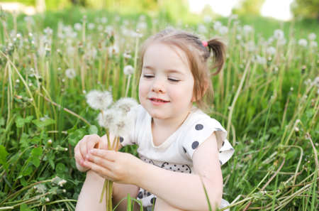 A little beautiful girl is sitting on the grass in a spring field among dandelions in the open air, enjoying nature. the concept of freedom