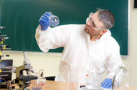 A chemist is engaged in the study of liquids in the laboratory.