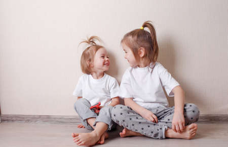 two little girls sit at home on the floor near the wall and play fun with each other. A fun and carefree childhood.