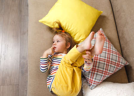 a little girl in yellow trousers and a bright T-shirt is lying on her back on the sofa with her legs up, biting her nails. Bad habits in children.