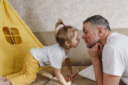 dad and little daughter play together at home on the couch, carefully examining each other Archivio Fotografico