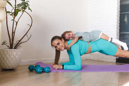 A young athletic mother and a girl do exercises together at home. Healthy development of parents and children, fitness and recreation. Imagens