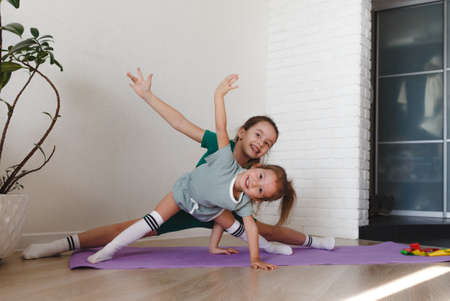 two little girls in sports uniforms are doing fitness at home