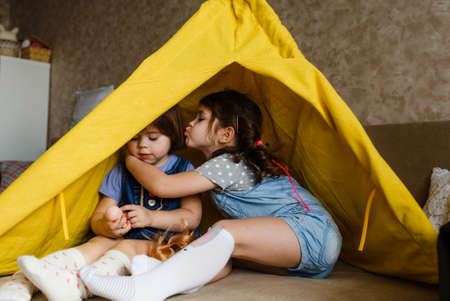 two little girls kiss each other on the cheek while sitting in a yellow teepee